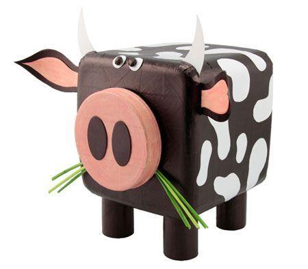 Для копилки для денег своими руками, вам понадобятся: две трубки из картона (например, от туалетной бумаги), пластиковый контейнер, пустая коробка, черный маркер, розовые краски, белая бумага, зеленая бумага, клейкая лента.
