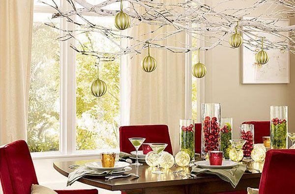 Интересным и очень необычным выглядит украшение не только самого праздничного стола, а и пространства над ним. Свисающие с веток новогодние игрушки создают максимально праздничное настроение.