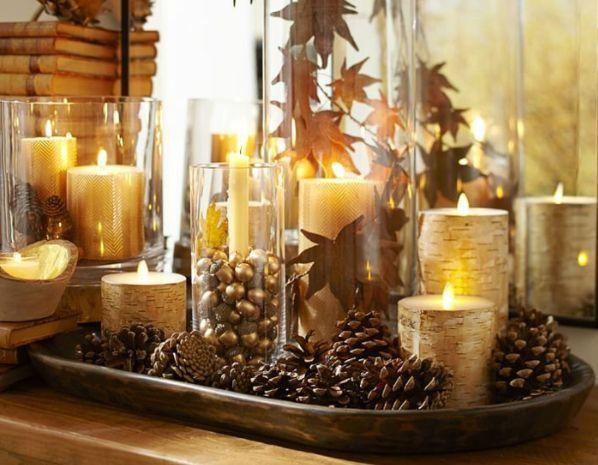 Золотистый цвет в сочетании с коричневыми шишками и желтыми светом свечей – отличное украшение для новогоднего стола. Для этого достаточно разместить шишки, свечи, бусы и любые другие элементы декора на подносе.