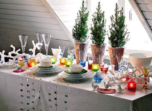 Очень популярным сейчас являются домашние елочки. Этими декоративными деревьями также можно очень удачно украсить новогодний стол. А расставленные на столе разноцветные свечи придадут вечерней трапезе особый шарм.