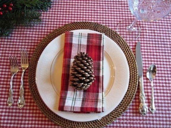 Ну и последний вариант для тех, кто не желает тратить много времени на украшение новогоднего стола. Салфетка в цвет скатерти и сосновая шишка на ней – вот и все, что напомнит хозяевам о причине торжества.