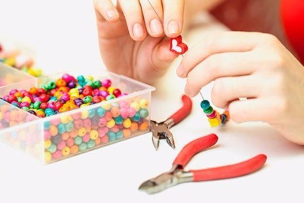 Ленточка и любые изделия, которые ребенок может на нее нанизывать (макаронные изделия, крупные пуговицы и т.д.). Получаются красивые бусики и кулончики.
