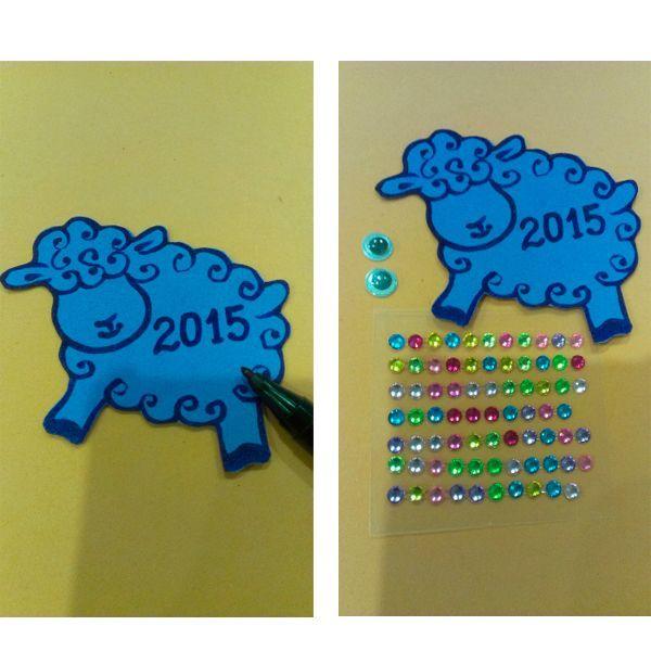 Перманентным маркером нужно нарисовать внутри силуэта детали - завитки, ножки, ушки. Написать цифры наступающего года 2015. Приготовить глазки и стразы для декора овечки.