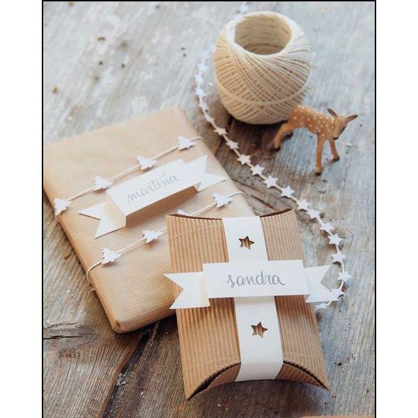 Из обычного белого картона можно вырезать объемные ярлычки с именами получателя. Получается очень необычно. Фон лучше использовать контрастный.
