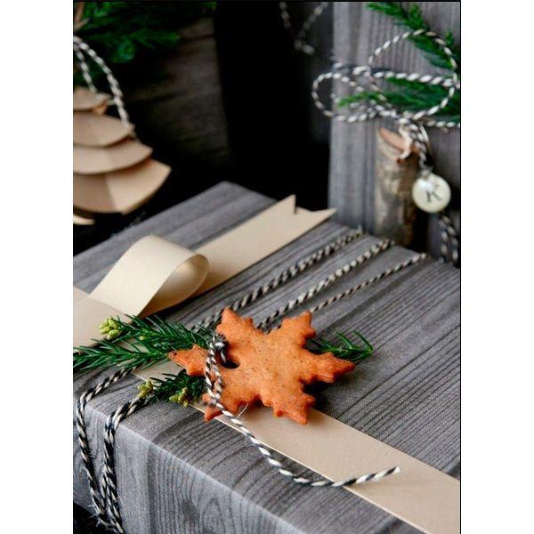 С помощью тесьмы или ленты можно привязать к упаковке пряник. Лучше всего для пряника выбрать характерную форму: елочку, снежинку и т.д.