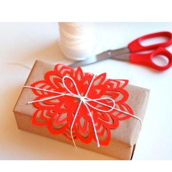 Если хочется украсить упаковку оригинально, но в наличии нет никаких элементов декора, можно за считанные минуты вырезать снежинку, которую бечевкой привязать к коробке с подарком. Получается очень красиво и необычно.