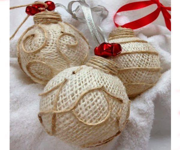Такие елочные игрушки можно сделать из старых шаров или перегоревших лампочек. Также понадобится термоклей, мешковина, бечевка или шпагат, тесьма для петельки.