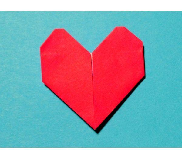 Нам понадобится лист цветной бумаги красного цвета. Вырезаем из него прямоугольный треугольник со сторонами 9 см. Из этого треугольника получится сердце 4,5 см. Кладем его на стол изнанкой кверху.