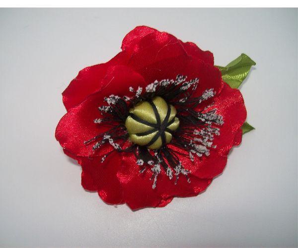 Заколка в виде цветка мака смотрится очень нарядно. Понадобится: атласная лента красного и зеленого цветов, черные нитки, манка, клей ПВА, вата.