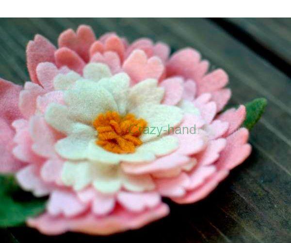 Для того чтобы сделать такую красивую брошку в виде цветка, вам понадобится фетр белого, розового, зеленого и оранжевого цветов, а также застежка.