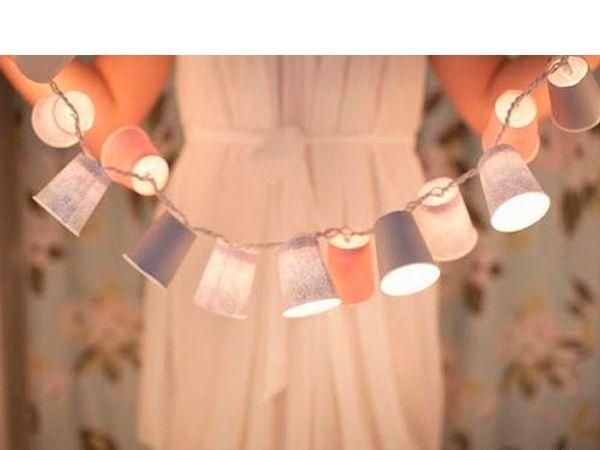 Из обычных пластиковых стаканчиков можно сделать красивую гирлянду. Понадобится: плотная цветная бумага или картон, гирлянда, стаканчики.