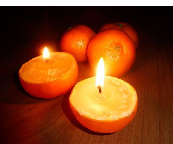 Апельсин разрежем пополам, ложкой очистим от мякоти. Разломаем на кусочки свечу, вытащим фитиль.