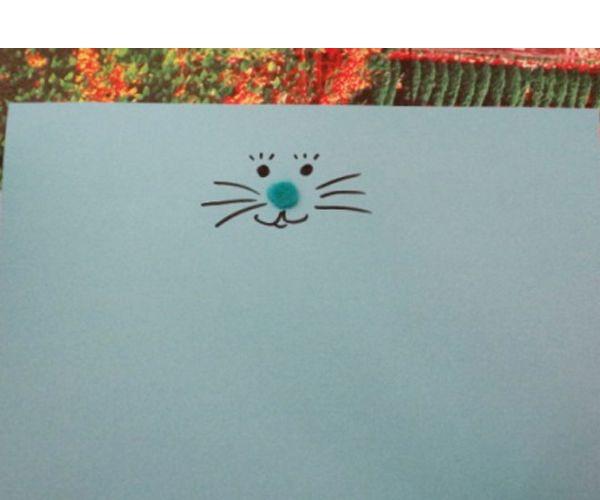 Возьмем прямоугольник цветной бумаги, сверху по центру нарисуем мордочку зайца, можно приклеить носик из фетра.