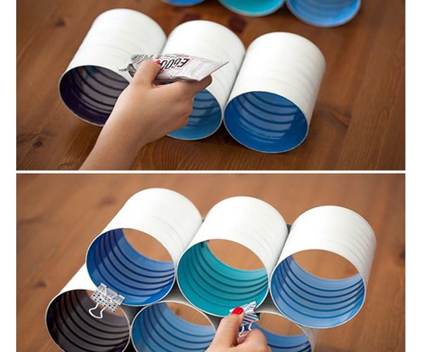 При помощи клея скрепите баночки между собой по три штуки стенка к стенке, зафиксируйте банки канцелярскими зажимами. Склейте таким же образом горизонтальные ряды своеобразной пирамидкой.