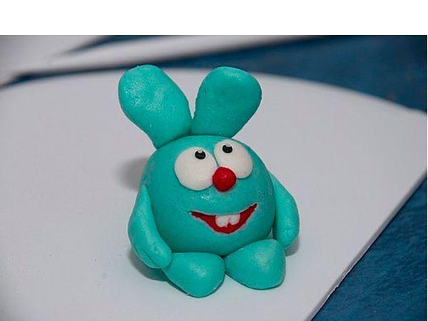К круглому туловищу прикрепите лапки и ушки из пластилина голубого цвета. Приплюсните два белых шарика — получатся глаза.