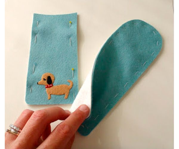 Рисуем выкройку для чехла, переносим ее на фетр, вырезаем. Приклеиваем аппликацию-собачку из фетра.