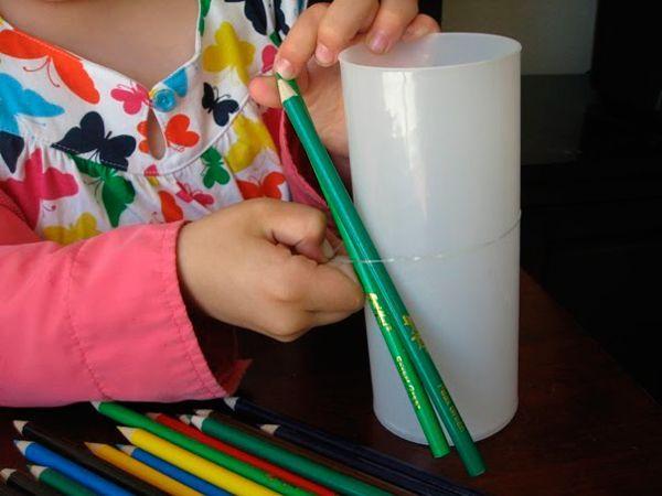 Понадобится высокий пластмассовый стакан или банка. Нужно надеть на него канцелярскую резинку и вкладывать под нее карандаши.