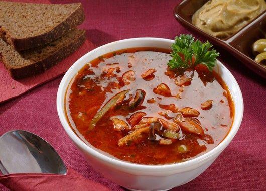 Солянка. Лук с морковью обжарить. Добавить копчености и томатную пасту. Залить водой, добавить картофель, кабачок, маринованные огурцы и зеленые помидоры. Варить до готовности, подавать со сметаной.