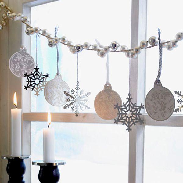 Окна на Новый год можно украсить народными игрушками. Поищите в местных сувенирных лавках куколки в костюмах, медвежат, исполненных вручную, или деревянные тотемы.