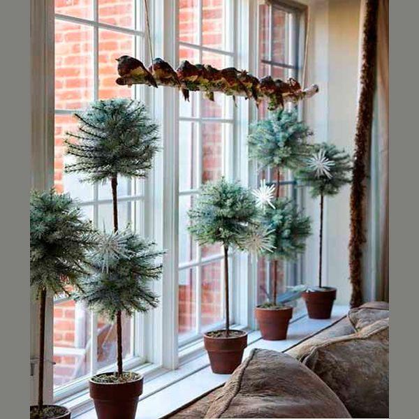 Подоконник — это сцена, на которую невольно обращают внимание все, входящие в дом. Его непременно украсят горшочки с настоящими хвойными растениями. Можно дополнить композицию елочными игрушками.