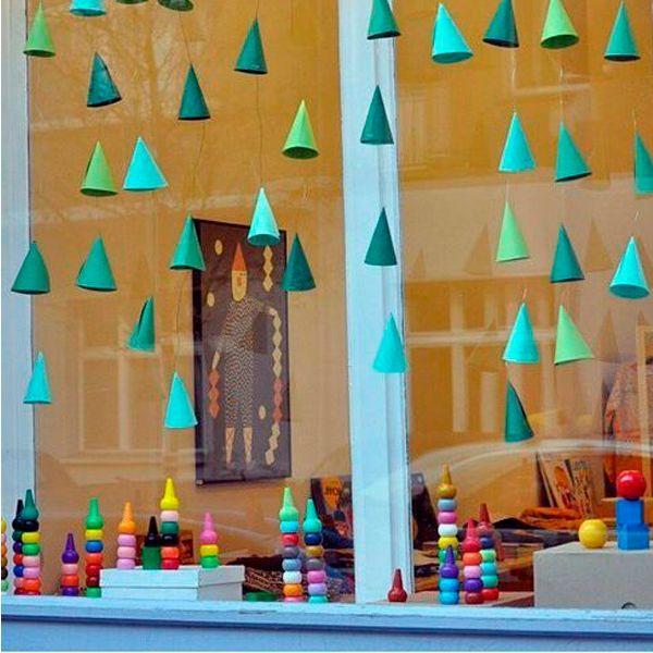 Елочки из картона можно сделать вместе с детьми. Они отлично подойдут для украшения окна в детской комнате. Чтобы создать иллюзию невесомости, нанижите елочки на тонкую леску.