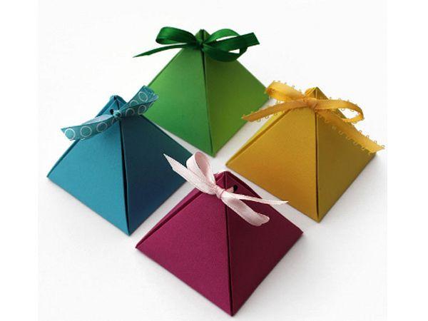 Сделаем оригинальные коробочки в форме пирамидок. Они могут служить упаковкой для ювелирных изделий. Понадобится плотная бумага, ножницы, дырокол и лента.