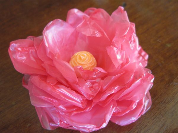 Таким цветком можно украсить штору или резинку для волос. Понадобится: картон, пакеты, ножницы, свеча, бусина или пуговица.