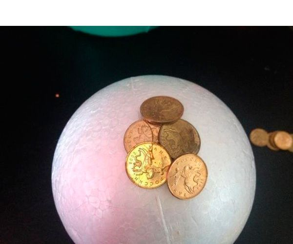 Берём наш шар и плотно обклеиваем его монетами, заходя монетами друг на друга. Если где-то остаются проплешины, не страшно, будем драпировать это в конце краской. Однако стараемся обклеивать без пробелов.