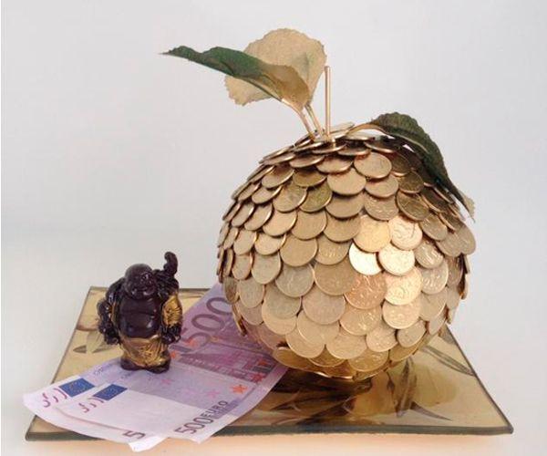 Для того чтобы сделать сувенир в виде яблочка, нам понадобится: шар-основа, монеты, термоклей, краска-спрей золотистого цвета, зубочистка, искусственные листья, подставка золотого цвета.